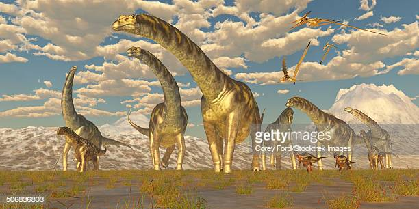 Hypsilophodon and pteranodon dinosaurs accompany a herd of Argentinosaurus.