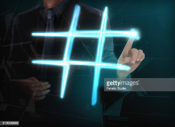 illustration of businessman making glowing hashtag on transparent screen - hashtag stock illustrations