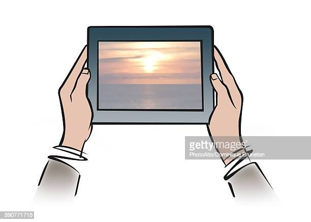 illustration of hands holding digital tablet showing tranquil sunset - social media stock illustrations