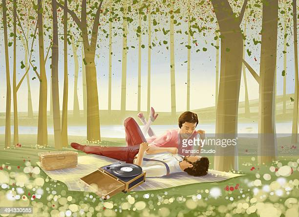 illustration of romantic couple lying on picnic blanket in forest - blanket stock illustrations, clip art, cartoons, & icons