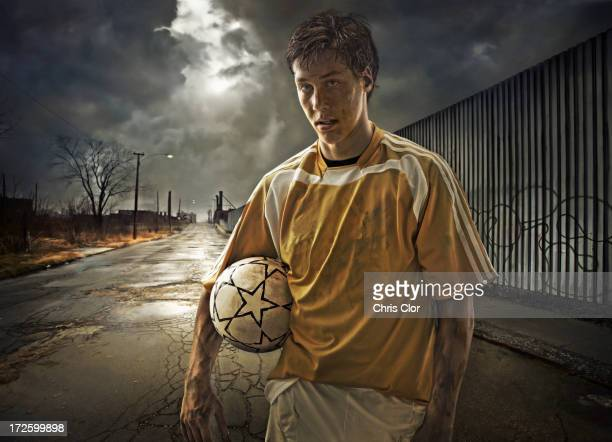 Illustration of soccer player holding ball on city street