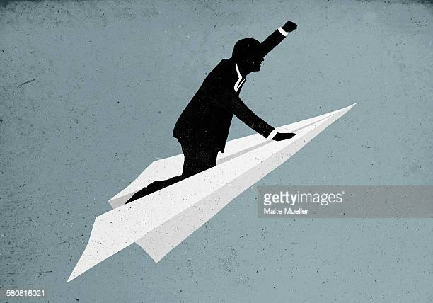 illustrative image of businessman flying on paper plane - business travel stock illustrations