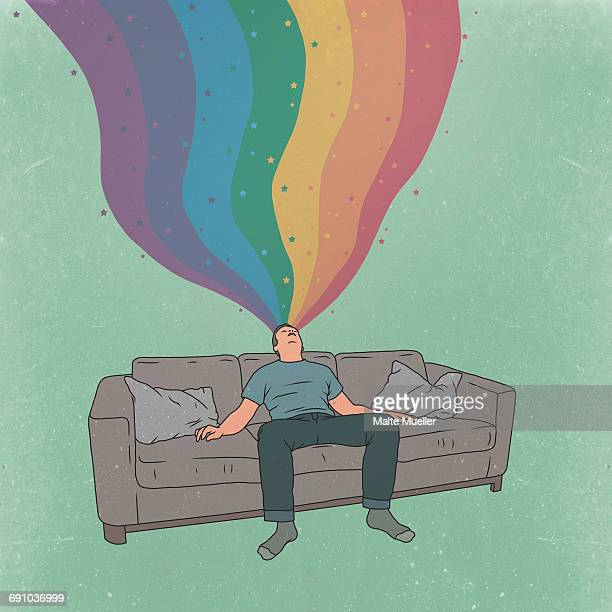 Illustrative image of tired man sleeping on sofa while dreaming about rainbow and stars
