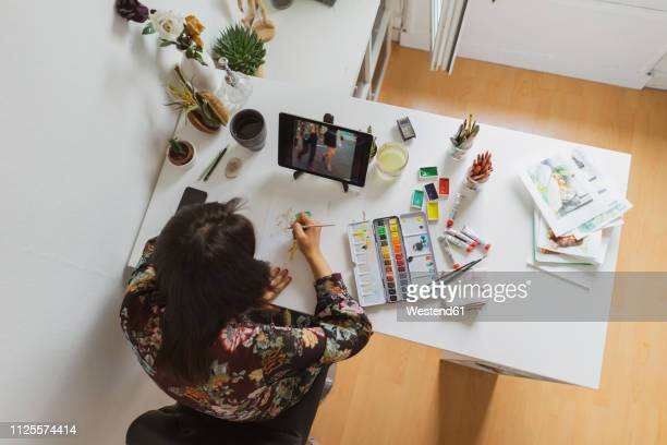 illustrator painting at work desk in an atelier using digital tablet, top view - floral pattern stock illustrations