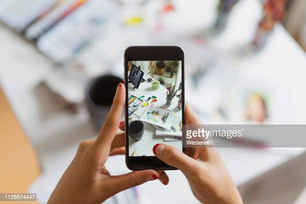 ilustraciones, imágenes clip art, dibujos animados e iconos de stock de illustrator's hands taking photo of work desk in atelier with smartphone, close-up - adulto de mediana edad