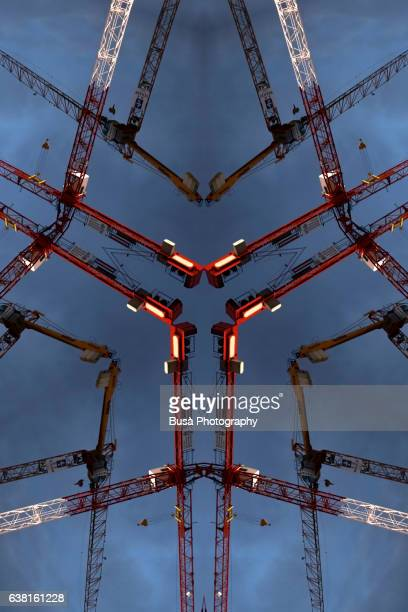 impossible architectures: digital manipulation of image of construction cranes against the sky. berlin, germany - housing development stock illustrations