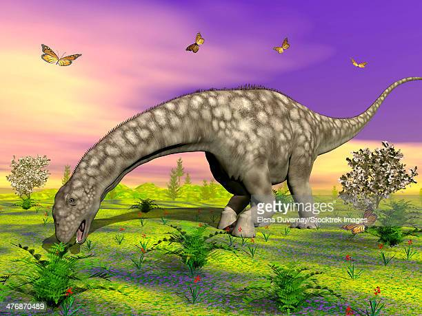 Large Argentinosaurus dinosaur eating small plants while surrounded with butterflies and flowers.