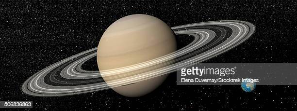 large planet saturn and its rings next to small planet earth. - next stock illustrations