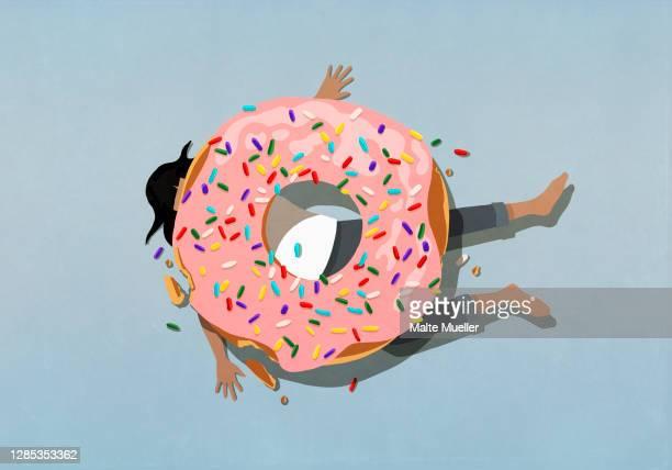 large sprinkle donut crushing woman - full length stock illustrations