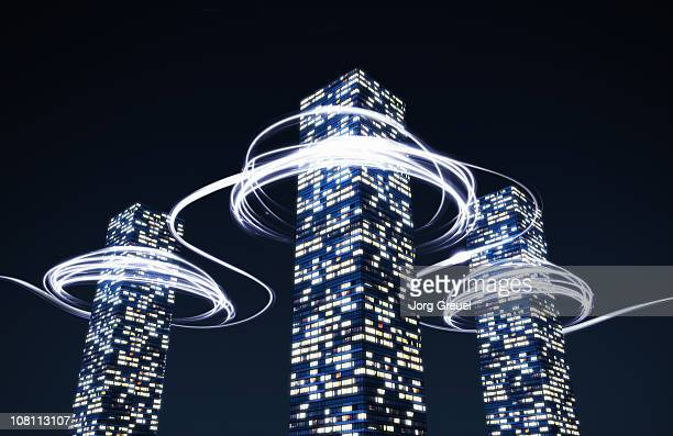 light trails around high-rise buildings - growth stock illustrations