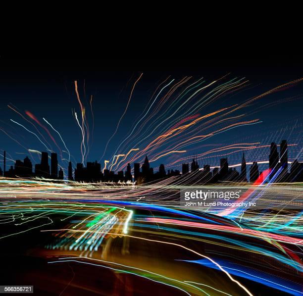 light trails near new york city skyline at night, new york, united states - digital enhancement stock illustrations