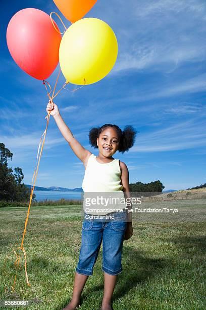 little girl standing, holding on to balloons