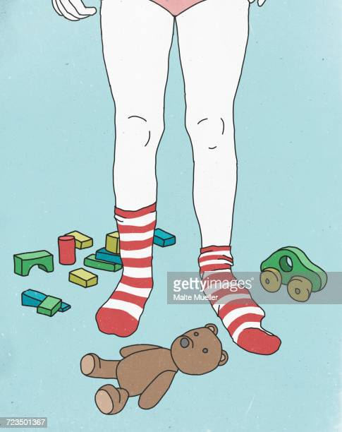 low section of girl wearing socks while surrounded by toys against colored background - toy stock illustrations