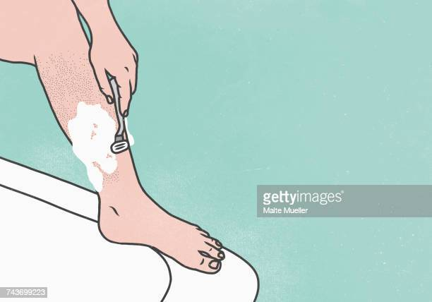 Low section of woman shaving leg on bathtub against green background