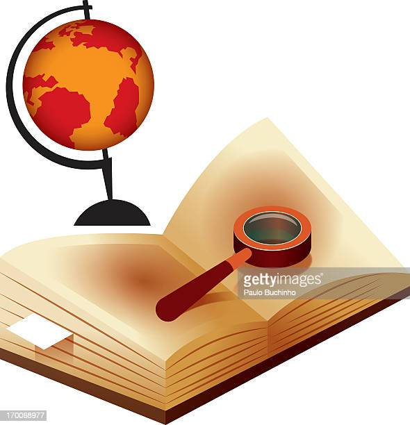 A magnifying glass on a book with a globe in the background