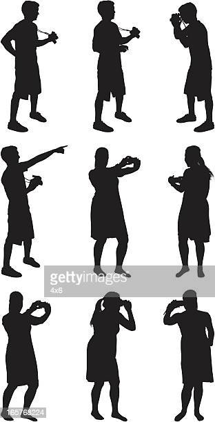 Male and female silhouettes with cameras taking pictures