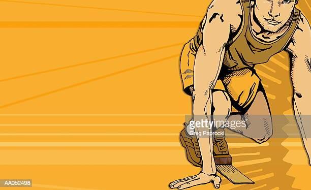Male runner crouching on starting block