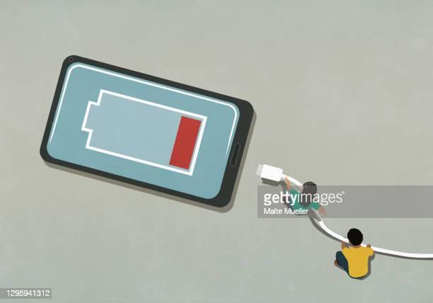 ilustrações de stock, clip art, desenhos animados e ícones de man and woman charging low battery smart phone - fornecimento de energia