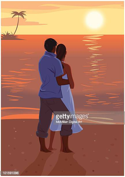 Man and woman standing on beach at sunset, rear view