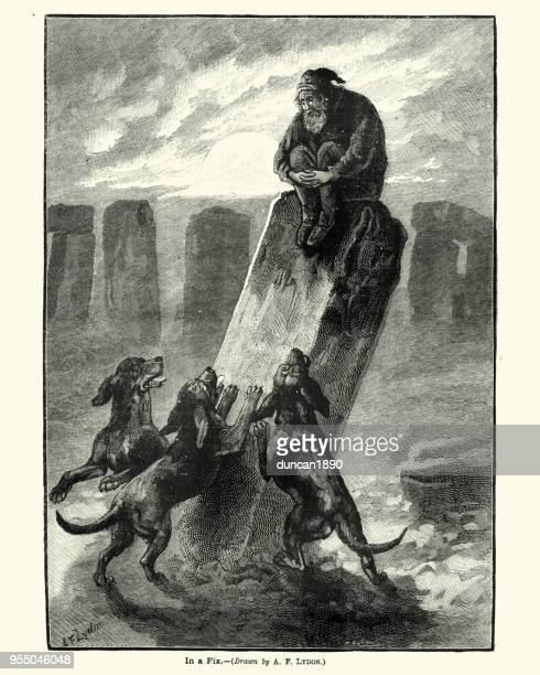 Man chased by a pack of dogs up a standing stone