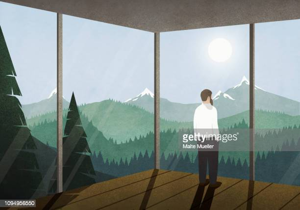 Man enjoying idyllic mountain view from house