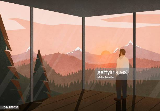 man enjoying tranquil view of sunset behind mountains from glass house - beauty stock illustrations