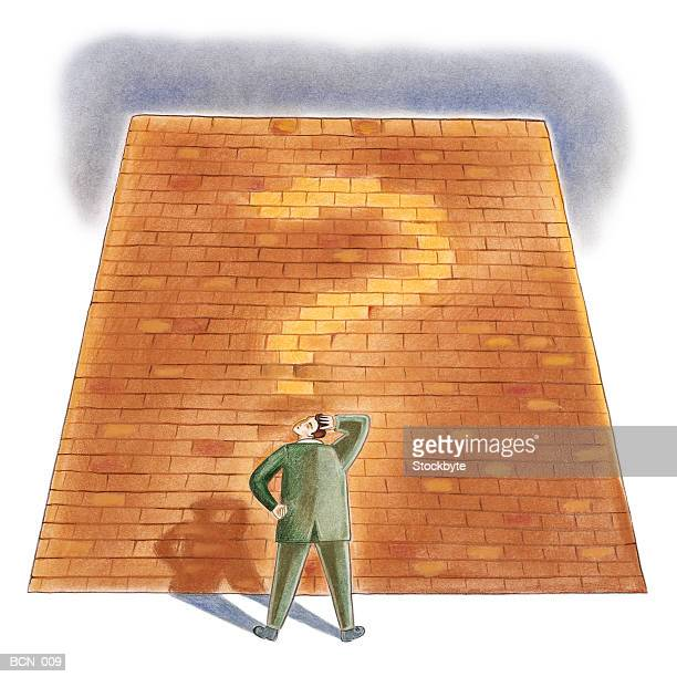 Man facing brick wall with question mark on it
