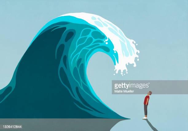 man facing huge ocean tidal wave - full length stock illustrations