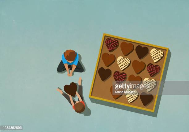 man giving heart shape chocolate to woman - scale stock illustrations