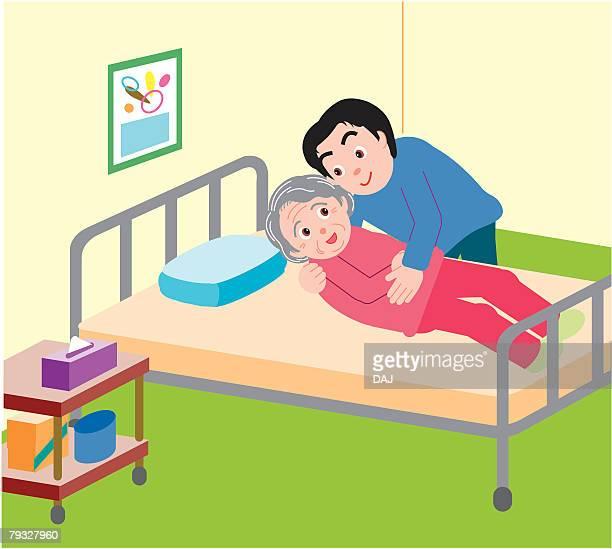 Man helping senior woman lying on bed, high angle view