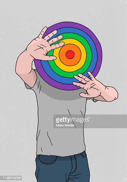 man hiding behind rainbow dart board - unrecognisable person stock illustrations