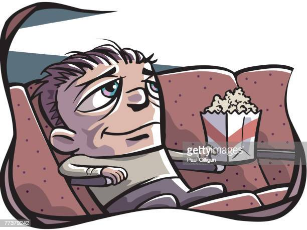 A man holding a bag of popcorns and watching a movie by himself