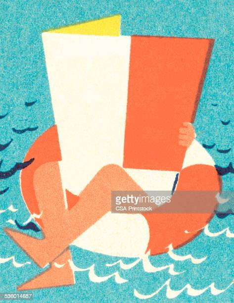 Man in inner tube with newspaper