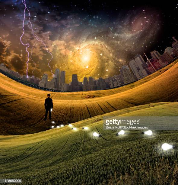 Man in surreal landscape. Light bulbs symbolizes ideas. Metropolis at the horizon. Vivid starry sky with galaxy