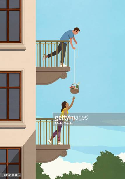 man lowering gift basket to woman below on apartment balcony - connection stock illustrations