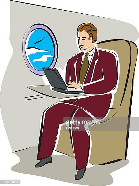 A man on an airplane with his laptop computer