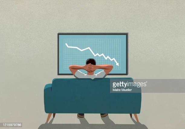 man on sofa watching stock market decline on tv - recession stock illustrations