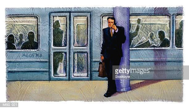 Man on subway platform using cellular phone