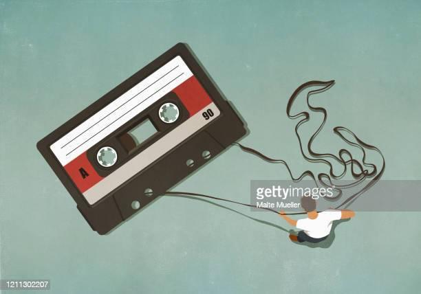 man pulling tape from large cassette - plastic stock illustrations