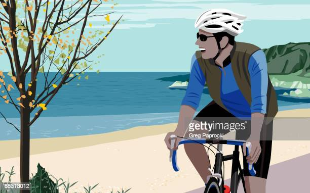 Man riding bicycle along beach