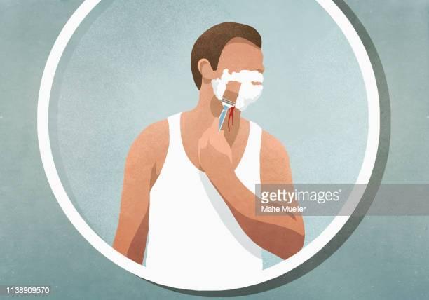 man shaving his face, bleeding in mirror - männliche person stock-grafiken, -clipart, -cartoons und -symbole