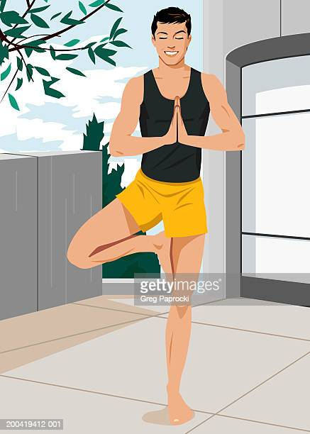 Man standing in yoga tree pose