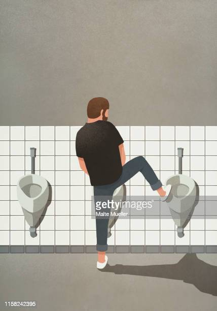 man urinating with leg up on urinal - bathroom stock illustrations