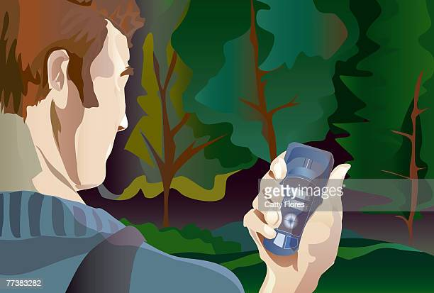 A man using a cell phone in a forest