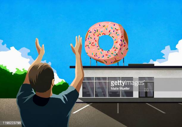 man with arms raised looking up at pink donut on top of bakery - outdoors stock illustrations
