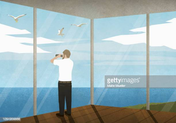 man with binoculars enjoying ocean view from beach house - looking at view stock illustrations