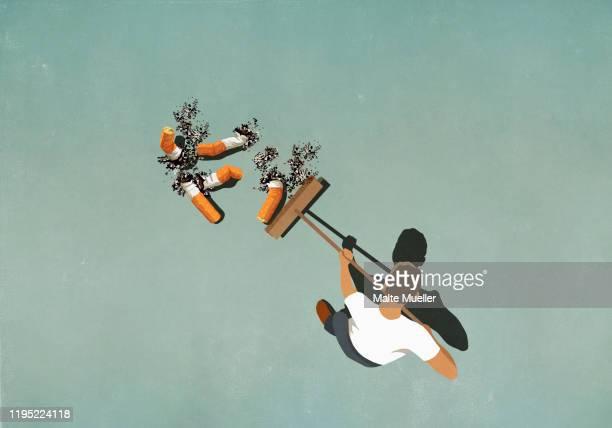 ilustraciones, imágenes clip art, dibujos animados e iconos de stock de man with broom sweeping up large cigarette butts - cigarrillo