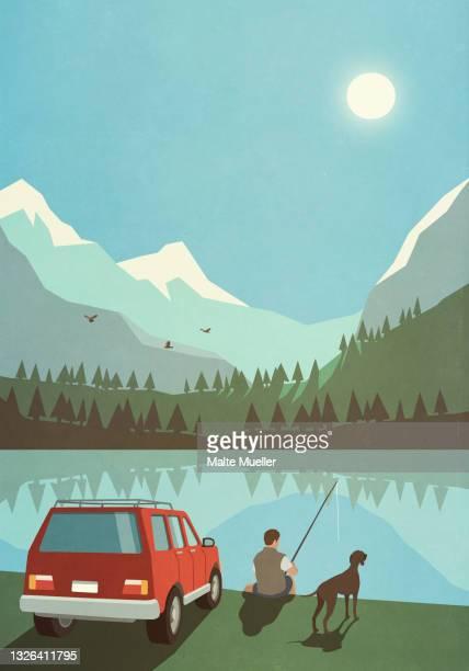 man with dog fishing at sunny idyllic mountain lake - leisure activity stock illustrations