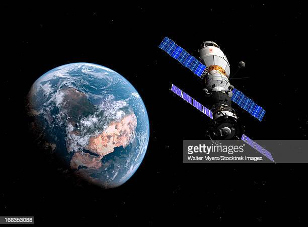 a manned soyuz tma-m spacecraft docked with an extended stay module. - orbiting stock illustrations