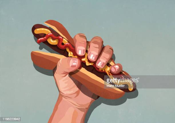 mans hand squeezing hot dog - unhealthy eating stock illustrations